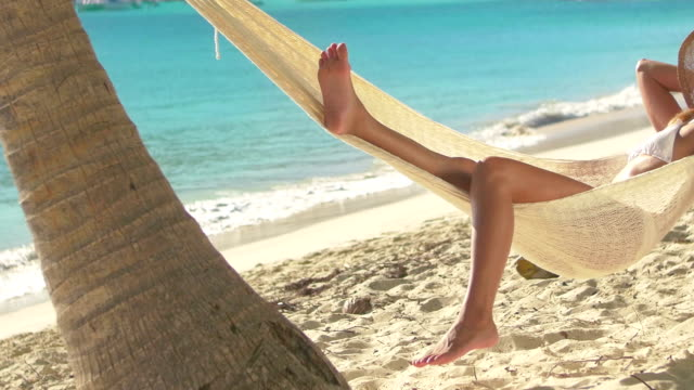 stockvideo's en b-roll-footage met video of a woman in hammock at the caribbean beach - gebruind