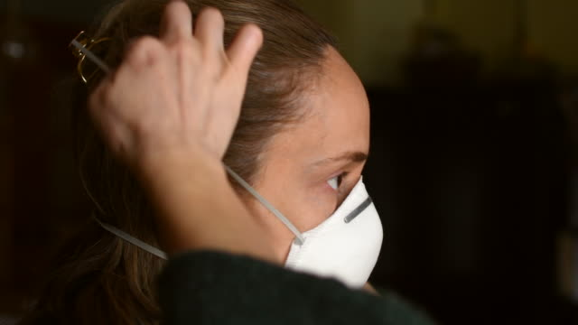 video of a woman putting on a n95 respirator. - adjusting stock videos & royalty-free footage