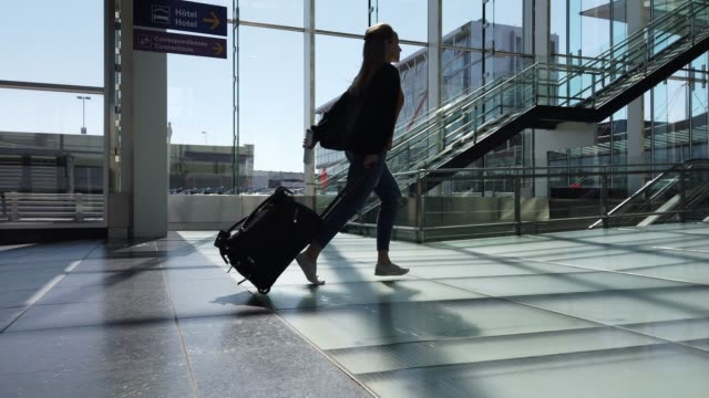 video of a woman running in an airport. - urgency stock videos & royalty-free footage