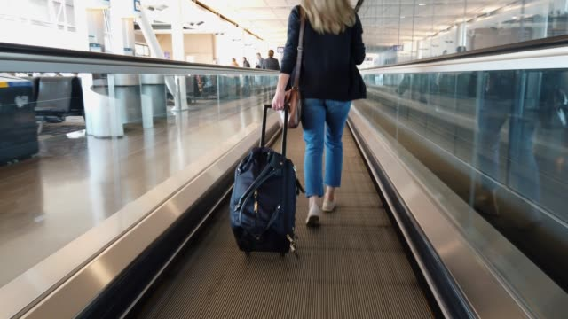 video of a woman running in an airport. - pedestrian walkway stock videos & royalty-free footage