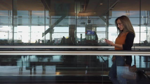 video of a woman standing on a moving walkway in an airport. - pedestrian walkway stock videos & royalty-free footage