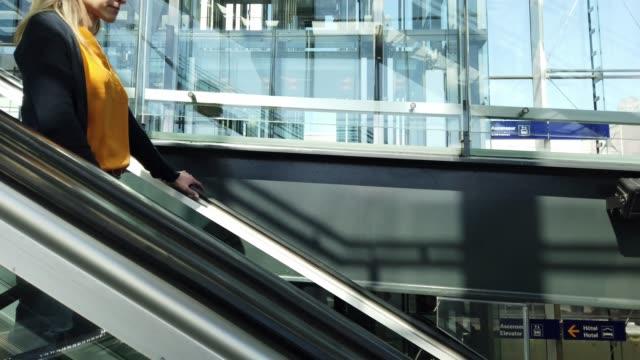 video einer frau, die in einem flughafen eine rolltreppe nimmt. - flugpassagier stock-videos und b-roll-filmmaterial