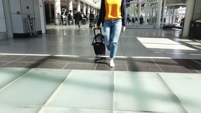 video of a woman walking in an airport. - carry on luggage stock videos and b-roll footage