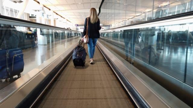 vidéos et rushes de vidéo d'une femme marchant dans un aéroport. - voie pédestre