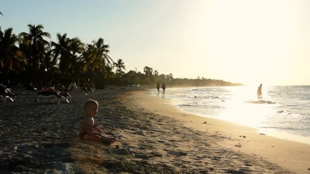 video of a young baby sitting in the sand by the beach. - varadero beach stock videos and b-roll footage
