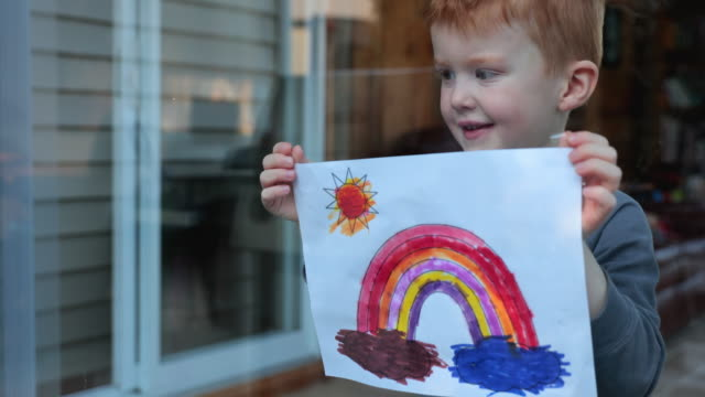 4k video of a young boy sticking his drawing on home window during the covid-19 crisis - rainbow stock videos & royalty-free footage