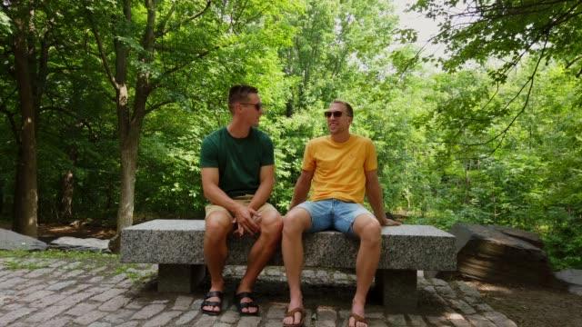 vídeos de stock e filmes b-roll de 4k video of a young homosexual couple talking on a park bench. - banco assento