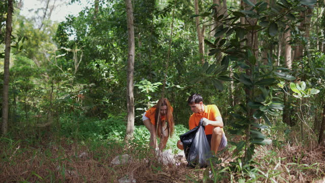 video of a young male and female volunteer picking up litter and chatting. - littering stock videos & royalty-free footage