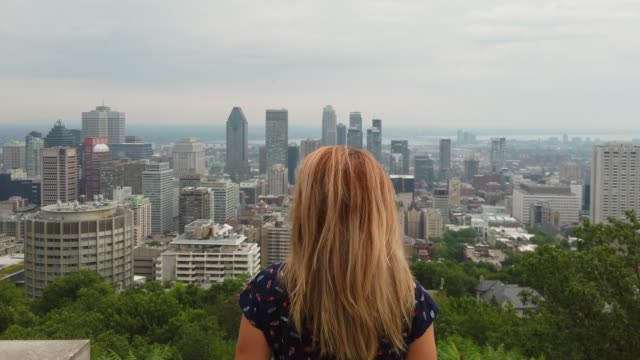 4k video of a young woman looking at montreal city. - guardare il paesaggio video stock e b–roll