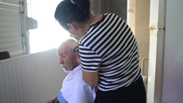 uhd video of adult woman cutting hair of senior adult man during coronavirus pandemic quarantine - selimaksan stock videos & royalty-free footage