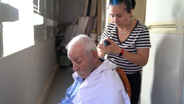 uhd video av vuxna kvinna klippa hår senior vuxen man under coronavirus pandemic karantän - selimaksan bildbanksvideor och videomaterial från bakom kulisserna