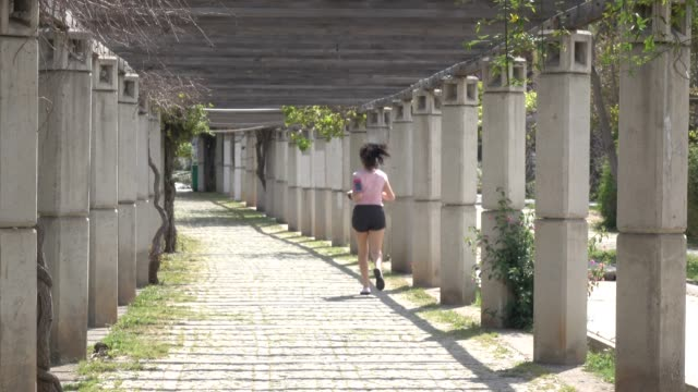 uhd video of adult woman running in public park - pink shirt stock videos and b-roll footage
