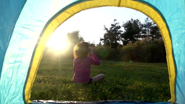 HD Video Of Adult Woman Sitting In Front Of Camping Tent In Springtime