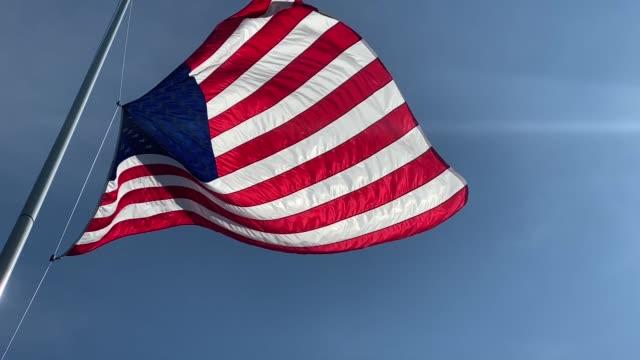 video of american flag blowing in the wind against a clear blue sky - 憲法点の映像素材/bロール