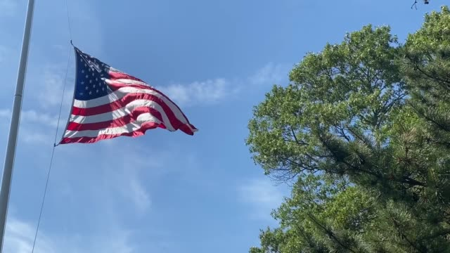 vídeos de stock e filmes b-roll de video of american flag blowing in the wind against a clear blue sky - cidadão