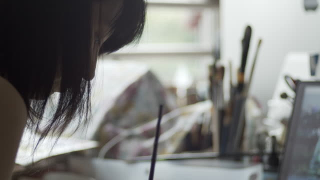 4k video of an asian woman painting in her atelier - back lit stock videos & royalty-free footage