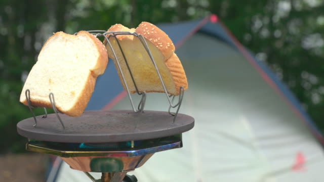 4k video of camp stove toaster rack with tent in background - toaster appliance stock videos & royalty-free footage