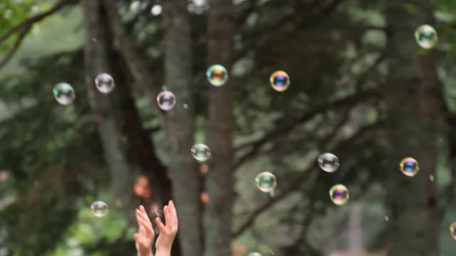 stockvideo's en b-roll-footage met video van kinderen proberen om zeepbellen te vangen. - soap sud