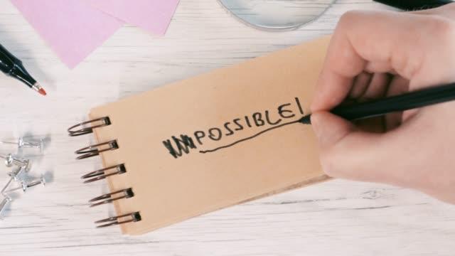 4k video der nahaufnahme einer männlichen hand schreibt unmöglich oder möglich auf notebook im büro - eventuell stock-videos und b-roll-filmmaterial