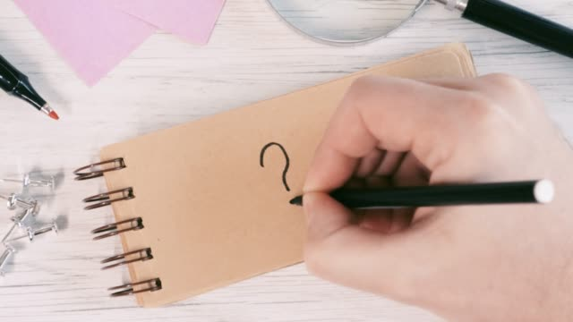 4k video of close-up of a male hand writes question mark on notebook in office - question mark stock videos & royalty-free footage