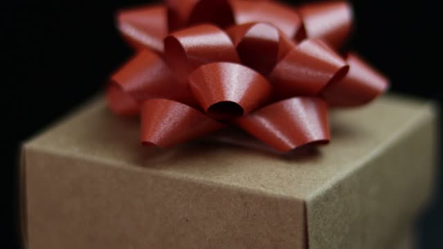 4k video of close-up rotating gift box and red ribbon on black background - gift box stock videos & royalty-free footage