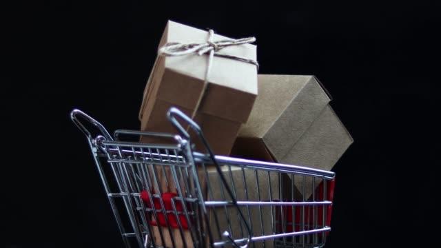 vídeos de stock e filmes b-roll de 4k video of close-up rotating shopping card and gift box on black background - viciado em compras