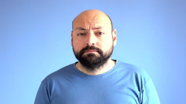 UHD vidéo de Compilation des Expressions faciales d'un homme adulte sur fond bleu