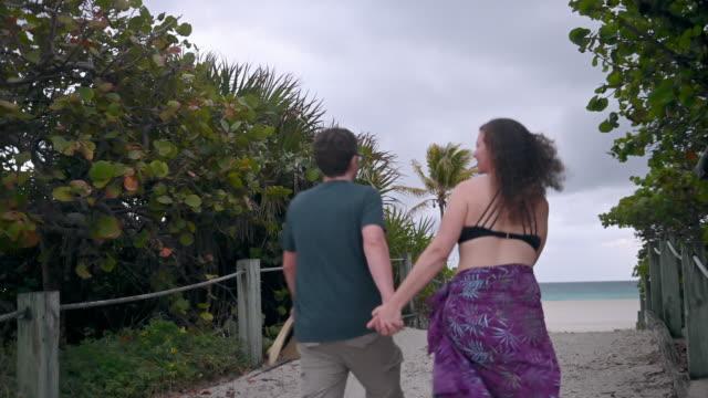 video von paar halten hände zu fuß zum strand im urlaub - body positivity stock-videos und b-roll-filmmaterial