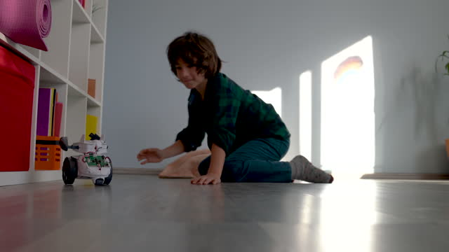 video of elementary schoolboy playing with toy robot at home - selimaksan stock videos & royalty-free footage