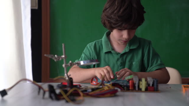 hd video of elementary schoolboy working on robotics and coding in front of green chalkboard - selimaksan stock videos & royalty-free footage