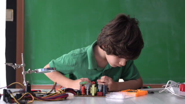 uhd video of elementary schoolboy working on robotics and coding in front of green chalkboard - selimaksan stock videos & royalty-free footage