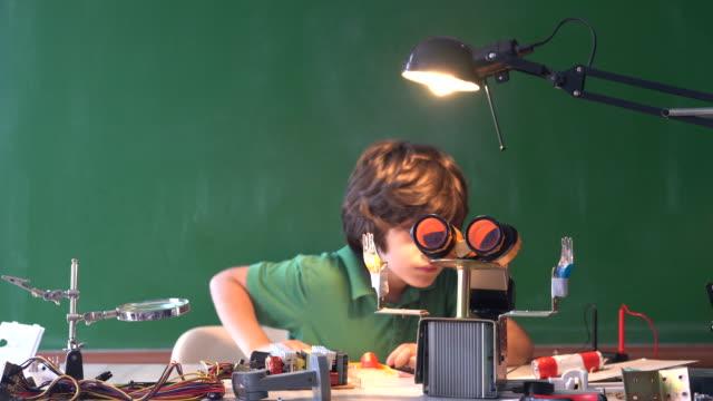 uhd video av grundskolepojke arbetar på robotics och kodning framför green chalkboard - selimaksan bildbanksvideor och videomaterial från bakom kulisserna