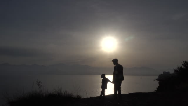 uhd video of father and son having chat in sunset - flat cap stock videos & royalty-free footage