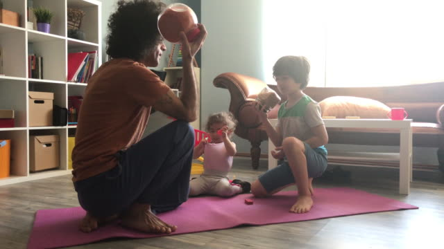 uhd video of father doing exercise while daughter and son playing around in living room - exercise room stock videos & royalty-free footage