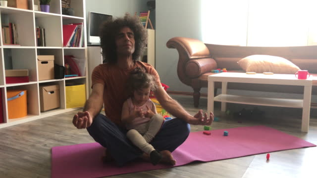 4k video of father doing yoga exercises while baby daughter playing around - zen like stock videos & royalty-free footage