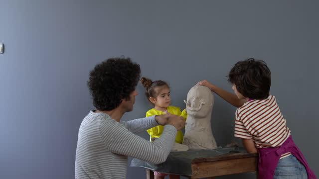 vidéos et rushes de vidéo du père, du fils et de la fille faisant de la sculpture - son