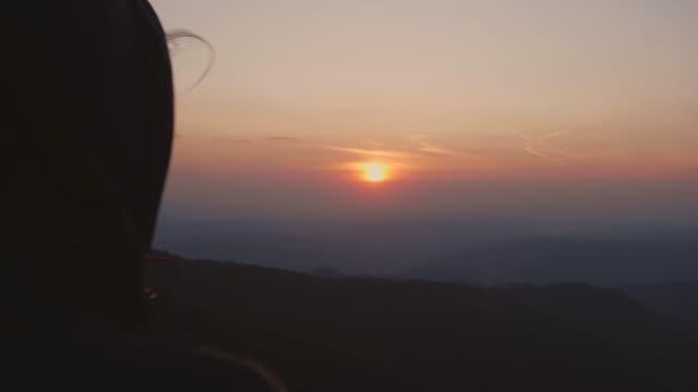 video von weiblichen wanderern, die den sonnenuntergang vom aussichtspunkt genießen - berggipfel stock-videos und b-roll-filmmaterial