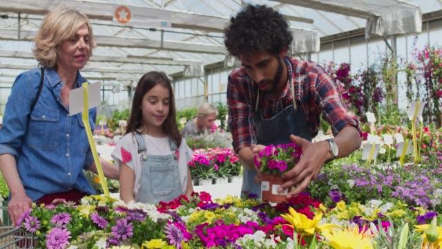 vidéos et rushes de vidéo de fille achat plante mère et travailleuse en garderie - fleuriste