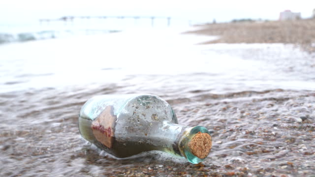 uhd video of glass bottle with label of covid-19 by sea wave on the beach sand - selimaksan stock videos & royalty-free footage