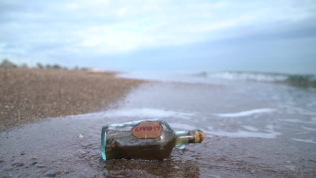 hd video of glass bottle with label of covid-19 by sea wave on the beach sand - selimaksan stock videos & royalty-free footage