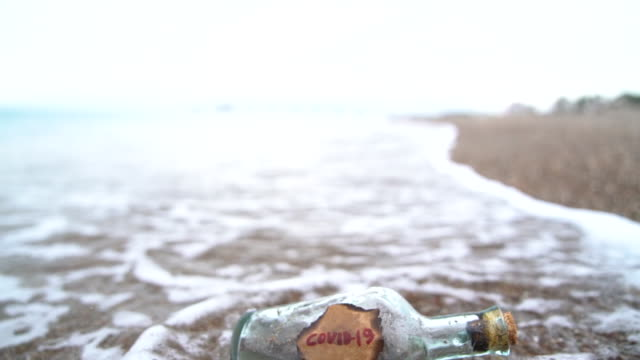 stockvideo's en b-roll-footage met hd video of glass bottle with label of covid-19 by sea wave on the beach sand - selimaksan