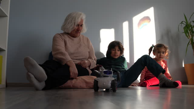 video of grandmother and grandchildren playing with toy robot in living room - selimaksan stock videos & royalty-free footage