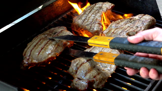 Video of grilling steaks on the fire-real slow motion