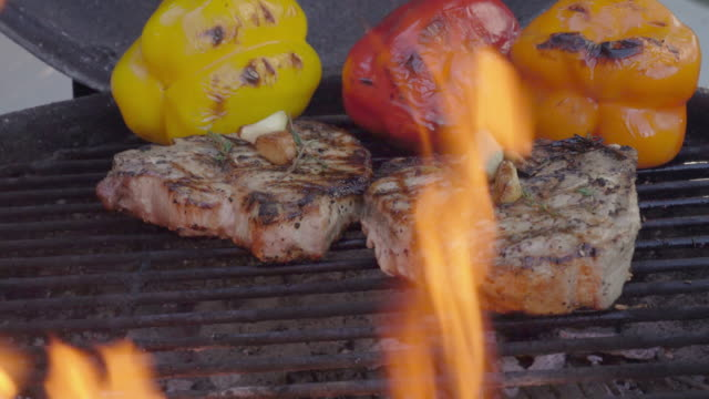 a video of ketogenic grilled bone-in pork chops, fully cooked with colorful roasted peppers, with hot, grill with flames - steak stock videos & royalty-free footage