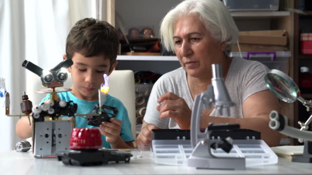 uhd video of little boy and grandmother building robot - manufacturing machinery stock videos & royalty-free footage