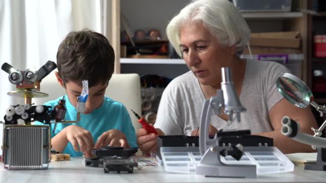 UHD-Video von kleinen Jungen und Großmutter bauen Roboter