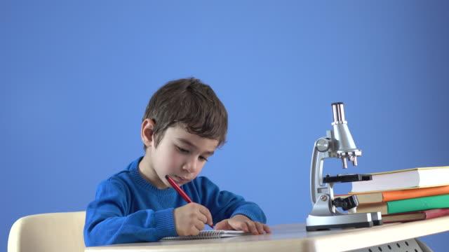 顕微鏡を使用して机の上の小さな男の子の UHD ビデオ