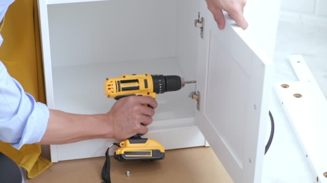 4k video of man carpenter doing renovation work at home drilling wood with drill electric screwdriver on locker - hardwood stock videos & royalty-free footage