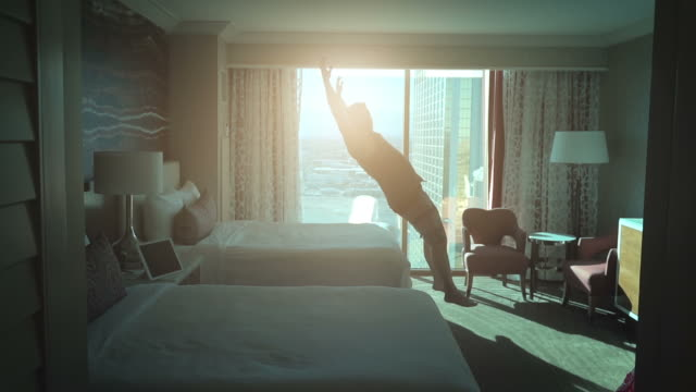 video of man jumping on the bed in real slow motion - ora di andare a letto video stock e b–roll