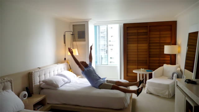 video of man jumping on the bed in slow motion - bed furniture stock videos & royalty-free footage